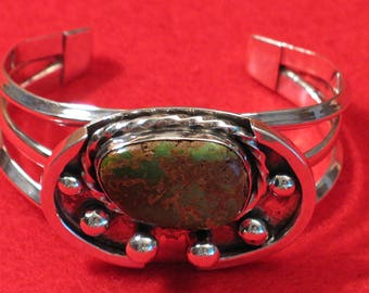 Silver cuff style bracelet with green turquoise cabochon