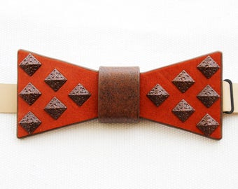 Leather bow tie with metallic pyramid studs.