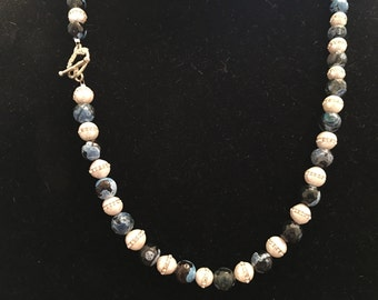24 inch necklace in silver with multi colored blue beads and white pearls embedded with Swarovski crystals.
