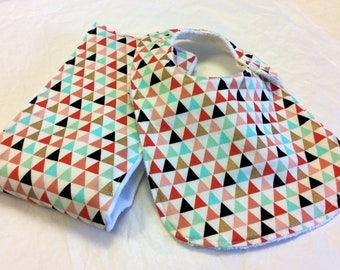 Tribal baby bib and burp cloth set in peach, mint, coral, black , and gold sparkle triangles on Oso Cozy diaper