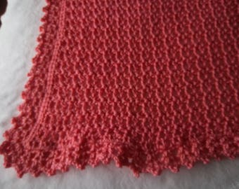 Coral colored crochet lap afghan for seniors.