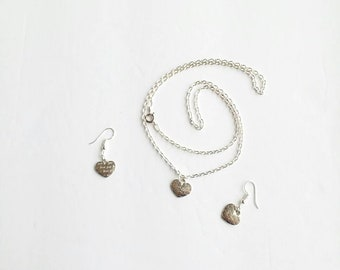 Sterling silver earrings and necklace with a heart shaped pendant that says loves you.