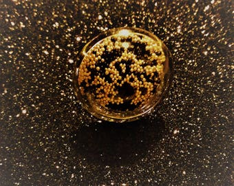 Globe ring in black and gold microbeads.