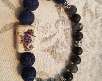 Lava bead oil diffuser bracelet in blue with snowflake obsidian and silver accents and a seahorse feature bead on a stretch cord
