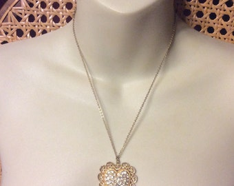 1960s heart shaped pendant with pave set rhinestones gold toned metal.