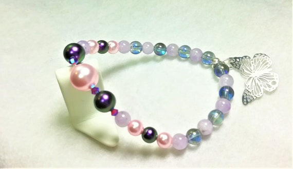 bracelet with pearly Swarovski beads, blue electroplated rock crystal,  ametrine and a butterfly shaped charm