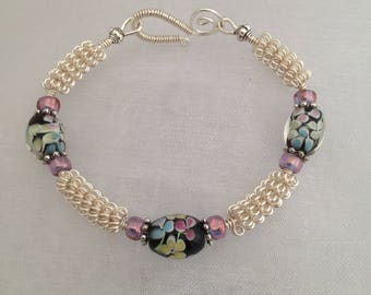 Silver wirework bracelet, with black floral lampwork beads.