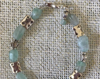 Aqua Sea Glass and silver bracelet.  Has sea turtles and silver plated hammered spacers.  8""