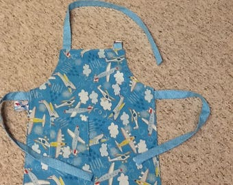 Airplanes child's apron. Aviation. Flying, clouds, helicopters, planes, pilots, blue, white, yellow, red, boy's apron. Reversible.