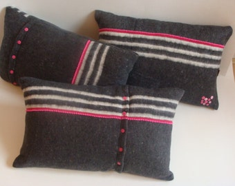 Set of 3 pillows from moving blanket with pink accents.