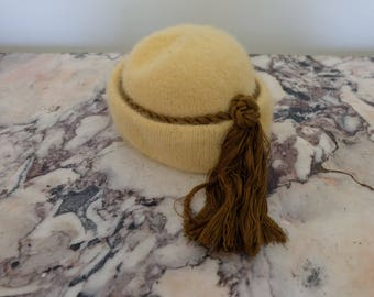 Vintage pastel yellow and brown fuzzy beanie hat with rope and tassel detail
