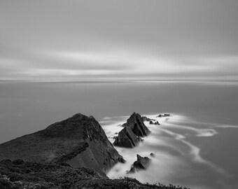 Black and white photograph of coastal rocks.