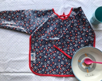 Bib with sleeves in blue coated cotton Navy with red and white flowers