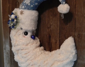 Blue snowflake Santa Moon with sparkly snowflake accents, cuddly rosebud beard, floral accents, and a snowball dangle with jingle bell.