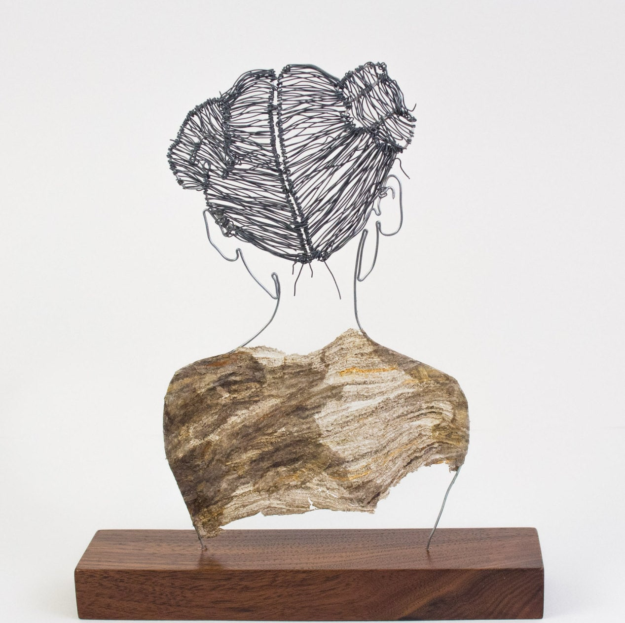 Wire woman figure sculpture with hair buns and paper wasp