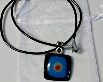 Fused glass pendant necklace; blue and black glass with orange flower millefiori