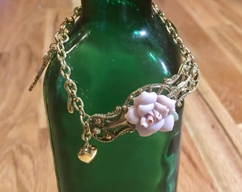 Pink and gold chain bracelet with charms