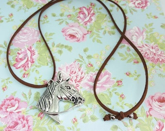 Lovely necklace with horse head pendant and a brown suede cord