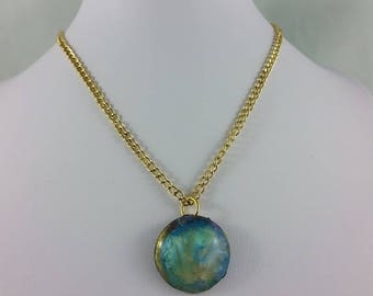 Necklace: opalescent resin pendant on golden chain