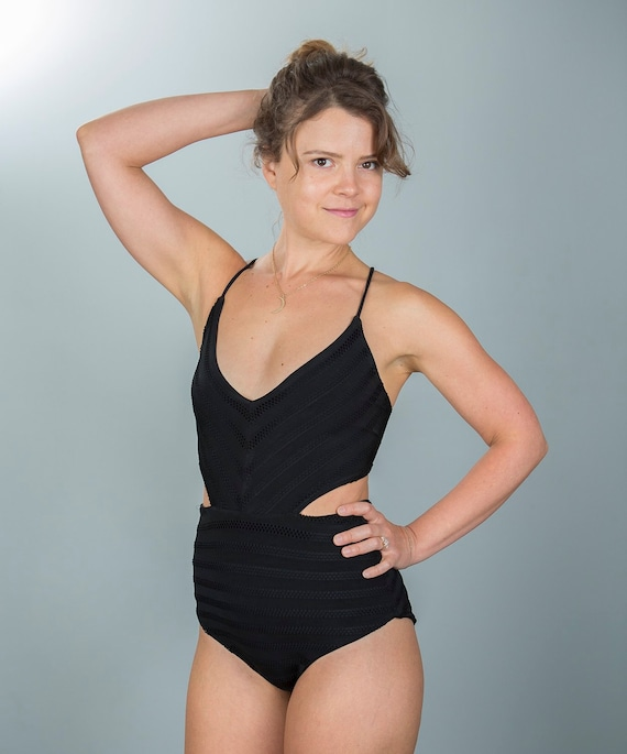 Black one piece with cut out sides laser cut stripes and lace up back
