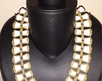 A monet parure gold tone and ivory like bracelet and bib necklace