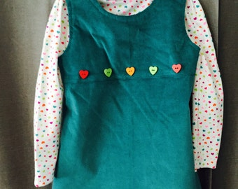 Corduroy jumper with colorful heart buttons.