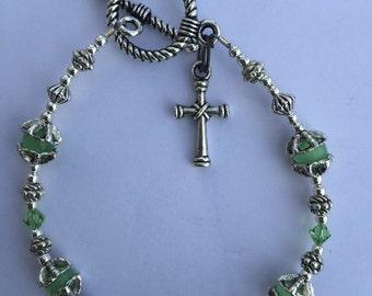 "Pale green swarovski crystal and cats eye beads cross bracelet. 7"""