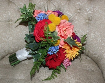Colorful boho garden bouquet in reds, purples, corals, pinks, yellows and blues. Real touch ferns and ivy. Loaded with roses.