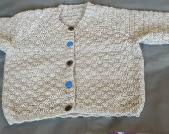 Child's grey cardigan with black and blue alternating buttons.
