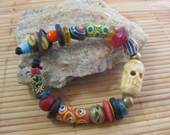 African trade bead bracelet with carved skull and featuring antique red Vaseline, King bead, and lost wax process brass beads