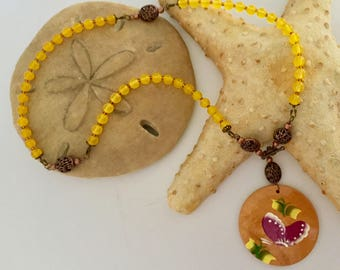 Butterfly yellow beaded necklace with copper accents and toggle enclosure