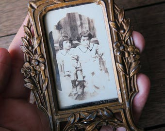 An antique small metal photo frame, simple frame to show eight plate size photos