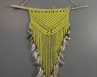 Yellow macrame wall, driftwood and feathers