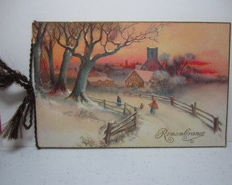 Vintage 1928 christmas card colorful graphics of a child and mother walking on snow covered country road church and town in the background