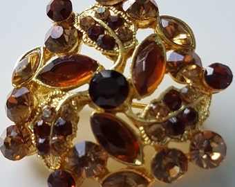 Vintage brooch in gorgeous gold and caramel shades of rhinestone on a gold tone background. Brown, gold, yellow