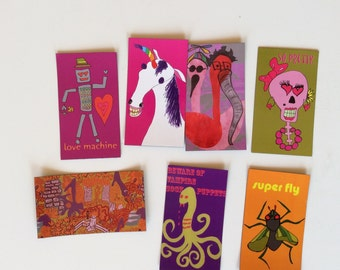 art magnets with drawings of animals and silly things like unicorns, robots, flamingoes, pugs, foxes, owls, and squirrels.