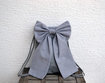 Gray drawstring backpack with a bow