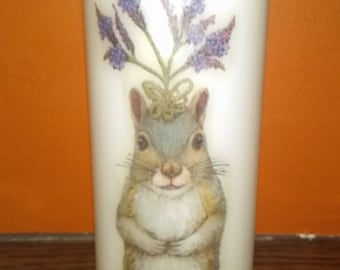 Medium white pillar candle with decoupaged floral crown wearing squirrel