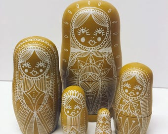 Mustard yellow nesting dolls, matryoshka dolls in dolls