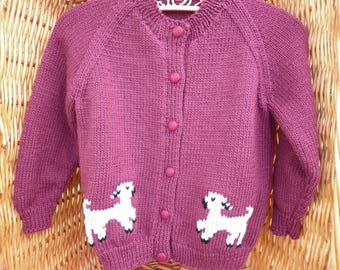 This girls' cardigan fits a 22 inch chest or a 2-3 year old. It is knitted in pale maroon colour and has lambs embroidered on front and back