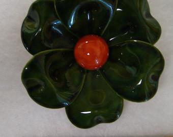 green and orange flower brooch.