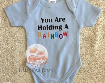 You are holding a rainbow onesie, rainbow baby onesie, rainbow bodysuit, new baby,