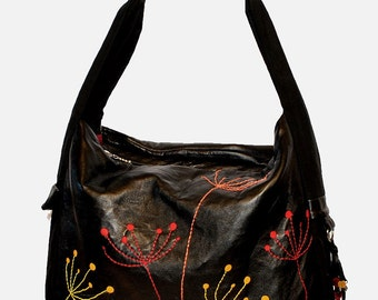 Large black bag with colorful floral motif. Shiny,soft genuine leather.