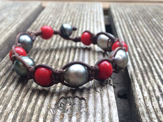 Bracelet of Tahitian pearls and red padre beads on Australian braided leather. Black pearls shamballa style bracelet. Colorful old red beads