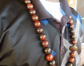 Men/women's 20 mm chunky brown wood beads necklace with clam shell. For African, Hip hop and traditional wear. About 36 inches all around.