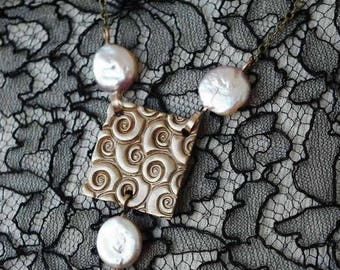 Artdeco necklace made of a square goldbronze piece  and  3 white sweetwater coinpearls . Can be made of silvercolour bronze  or copper too