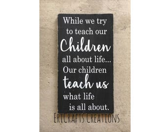 While we try to teach our children all about life Wood Painted Sign