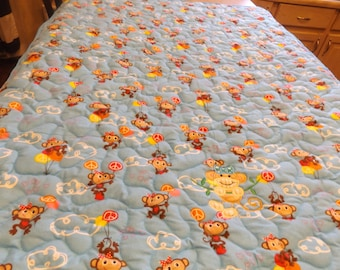 Baby Blanket with monkeys and appliqued monkey swinging on a vine.