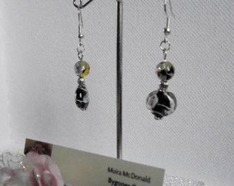 Glass lampwork bead drop earrings for pierced ears. Black earrings with pink swirls.