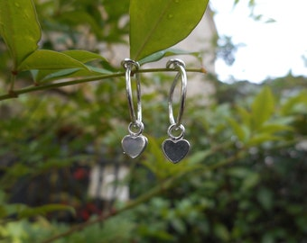 Pair of small, delicate, minimalist sterling silver hoop earrings with heart charms